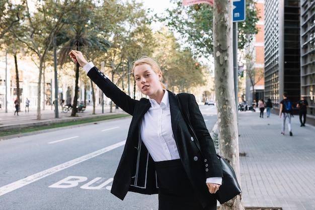 Die vorderansicht der jungen geschäftsfrau stehend auf der straße hagelt ein taxitaxi
