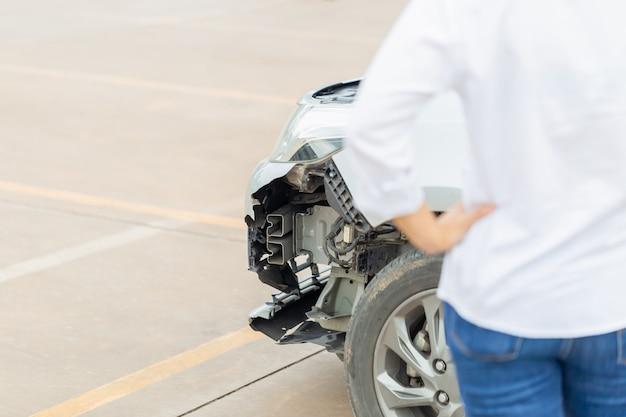 Die vorderseite des autos wird beschädigt, während eine junge frau nach einem autounfall am beschädigten auto steht