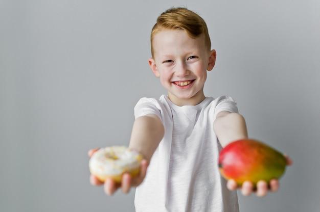 Die wahl zwischen gesunden und ungesunden lebensmitteln. das kind hält einen donut und eine mango
