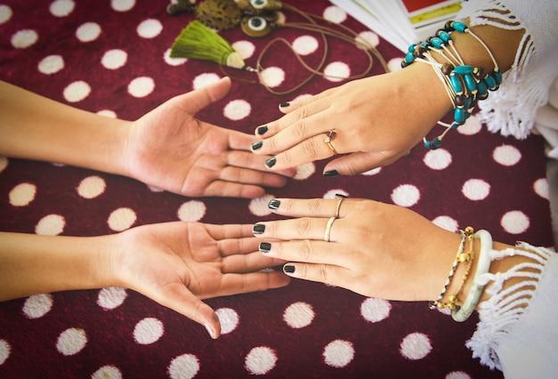 Die wahrsagerin, die an hand vermögenslinien liest, palmistry psychic-lesungs-hellsehen übergibt konzept mit tarockkarten weissagung