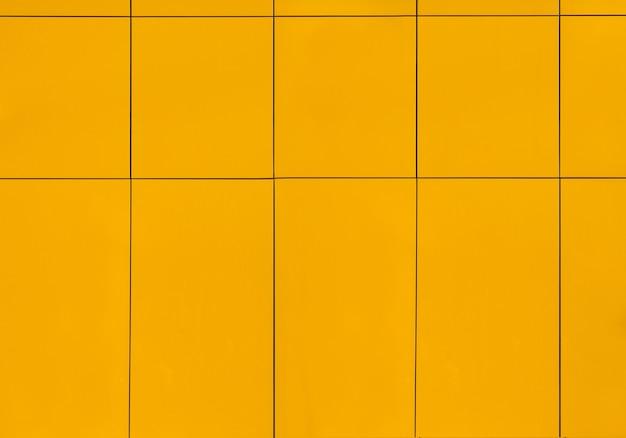 Die wand des hauses draußen ist mit gelben keramikfliesen bedeckt, hintergrundnahaufnahme