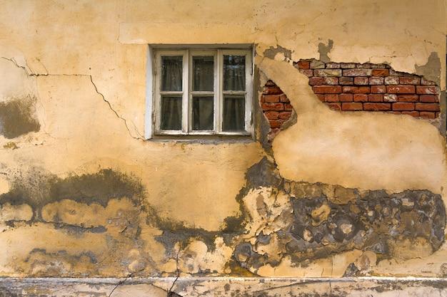 Die wand eines alten hauses mit einem fenster. die wand muss repariert werden, zusammengebrochener putz und mauerwerk.