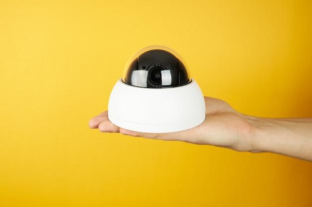 Die warte-cctv-überwachungskamera an der handfläche auf einem gelb mit kopierraum. sicherheits- und datenschutzkonzept