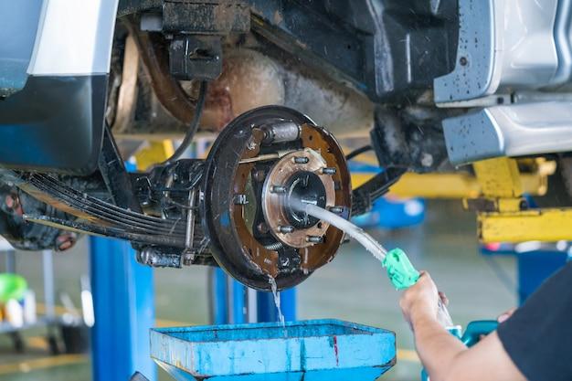 Die waschende trommelbremse der arbeitskraft eines autos unter einem hochdruck in der garage.