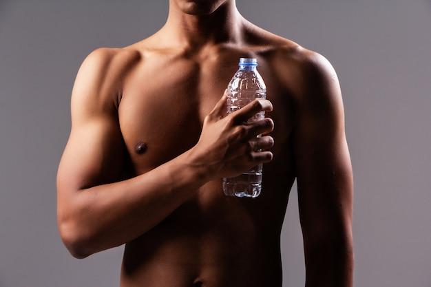 Die wasserflasche hielt sich mit der menschlichen hand vor dem körper fest