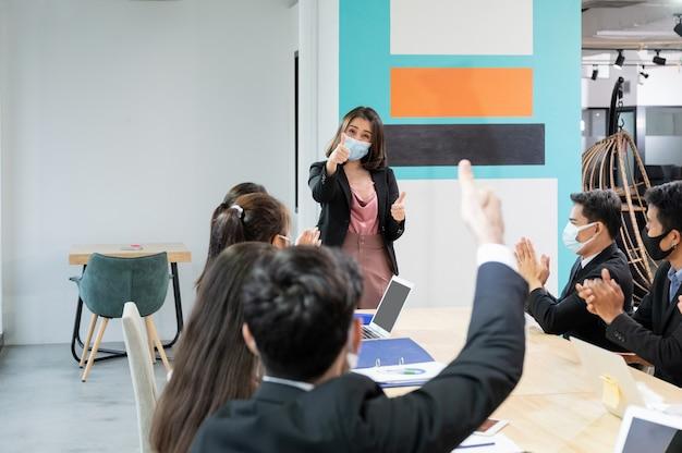 Die weibliche führungskraft, die daumen hoch zeigt, stimmt zu, die meinung der kollegin während des treffens in einem neuen normalen büro zu unterstützen