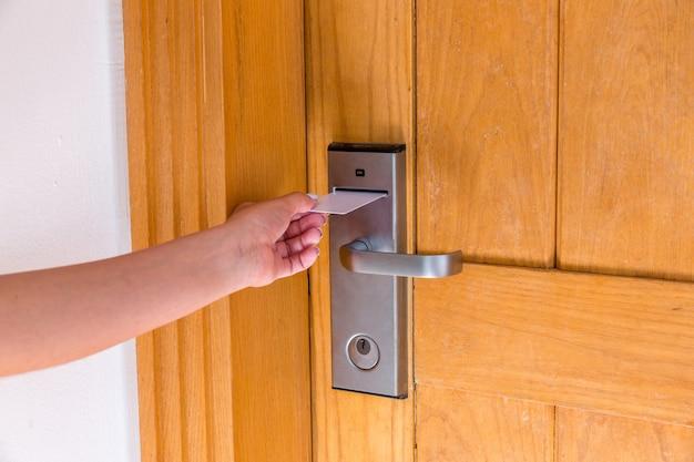 Die weibliche hand, die magnetschlüsselkarte setzt und hält, schalten ein, um hotelzimmertür zu öffnen