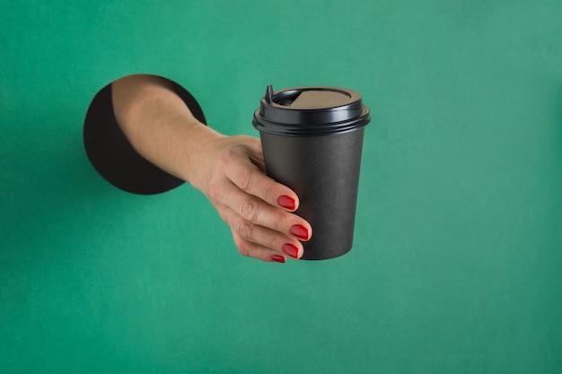 Die weibliche hand, die papierkaffeetasse hält, lokalisierte rundes loch im grünbuch.