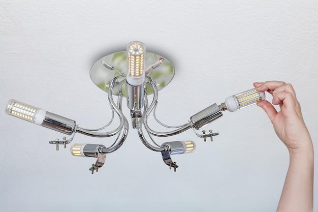 Die weibliche hand ersetzt die lampen im raumleuchter und installiert eine led-maislampe im lampenhalter.