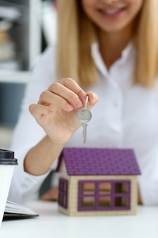 Die weibliche hand hält den schlüssel zum schloss in der hand