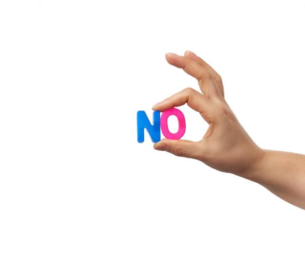Die weibliche hand hält zwei plastikbuchstaben mit dem wort nein, dem konzept der verleugnung