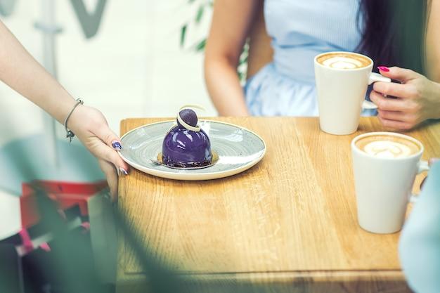 Die weibliche hand legt das stück kuchen im café auf den tisch.