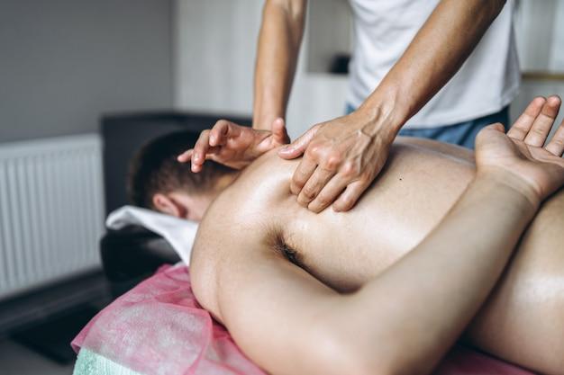 Die weibliche masseuse gibt dem mann, der auf der massageliege liegt, eine rückenmassage