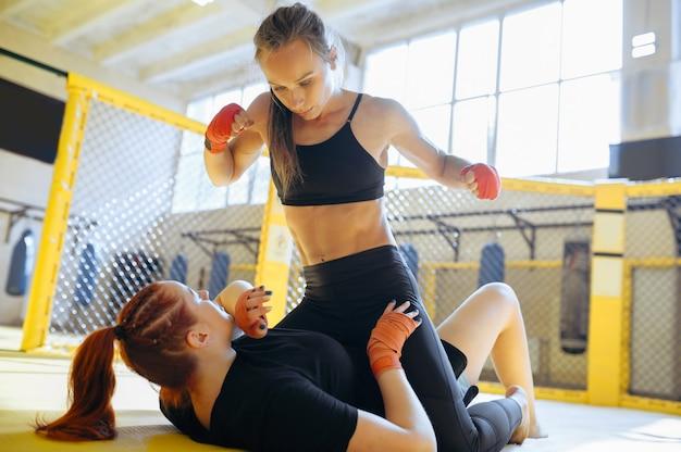 Die weibliche mma-kämpferin beendet ihre gegnerin in einem käfig im fitnessstudio.