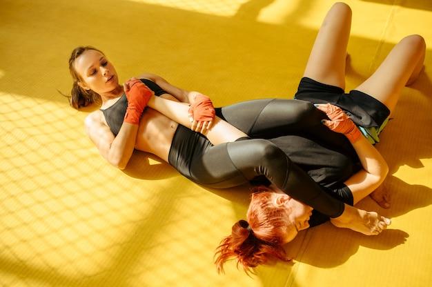 Die weibliche mma-kämpferin führt ihrem gegner in einem käfig im fitnessstudio einen schmerzhaften handgriff zu.