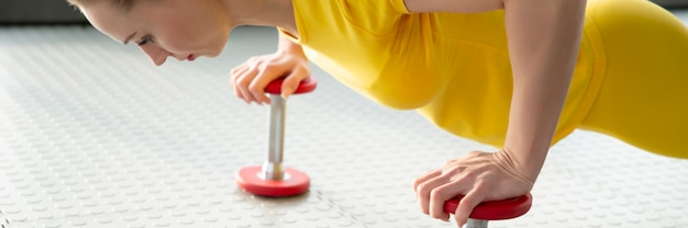 Die weiblichen hände, die dummkopf halten, trainieren die gewichte, die auf dem boden in der turnhalle stehen