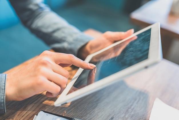 Die weiblichen hände, die mit einem tablet arbeiten