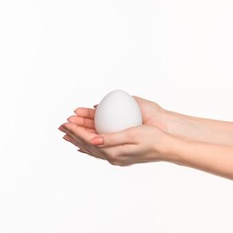 Die weiblichen hände halten ein weißes ei auf weiß.
