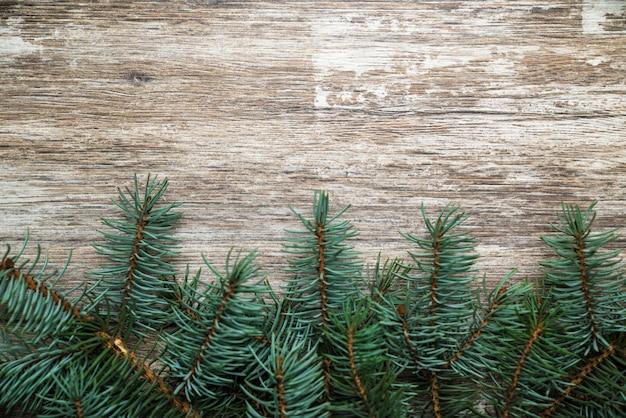 Die weihnachtsbaumzweige liegen auf alten, dunklen brettern.