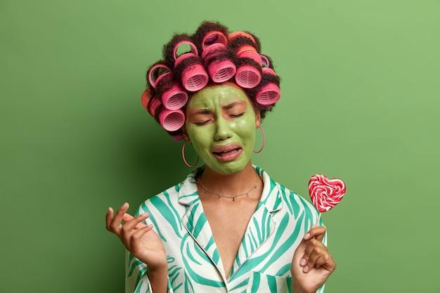 Die weinende verzweifelte frau neigt den kopf und drückt negative emotionen aus, wendet eine gesichtspflege-maske an, lockenwickler, hält köstliche süßigkeiten, hat schlechte laune, vermeidet den verzehr von zucker und hält sich an die diät, isoliert auf grün