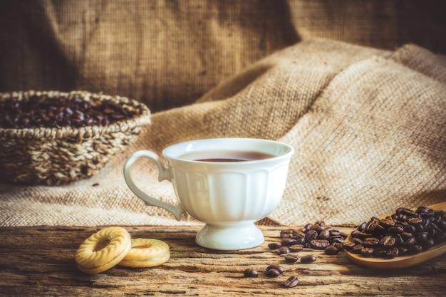 Die weinleseart eines hölzernen blattes der weißen kaffeetasse und der kaffeebohnen altes sackleinen.