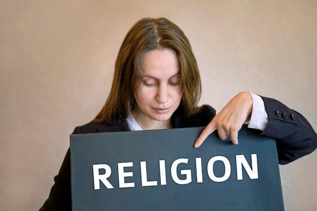 Die weiße frau steht auf und zeigt mit dem finger auf die inschrift religion auf der tafel