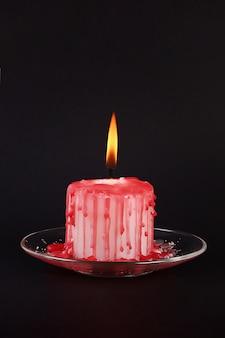 Die weiße kerze diy halloween, die im roten wachs bedeckt wird, mögen blutstropfen auf schwarzem hintergrund
