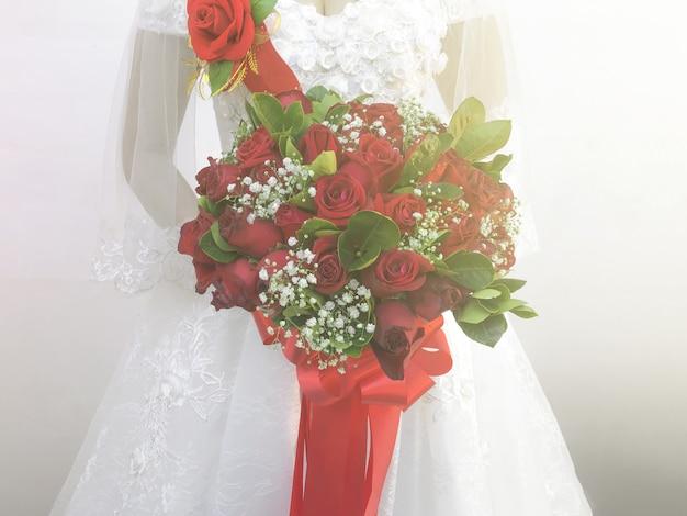 Die weiße kleiderbraut, die rosenblumenstrauß mit heller wand als hintergrund hält.