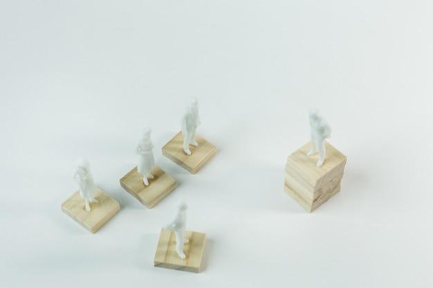 Die weiße menschliche miniatur auf hölzernem plattenabschluß herauf bild.