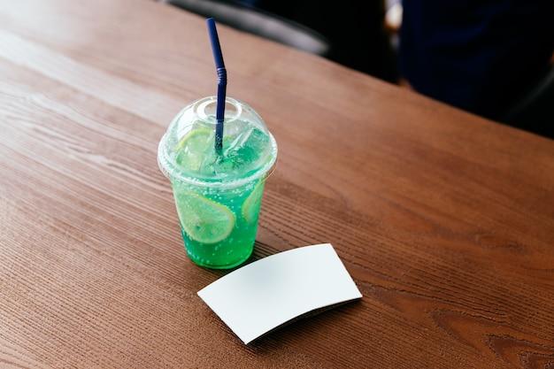 Die weiße tassenhülle aus grünem soda mit geschnittener zitrone auf einem holztisch. schalenärmelschablone.