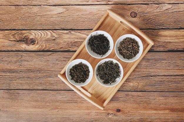 Die weißen trinkschalen des sortiments des trockenen tees, um auf hölzernem hintergrund zu bestellen