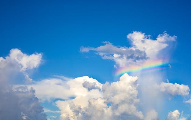 Die weißen wolken haben tagsüber bunte regenbogen am strahlend blauen himmel.