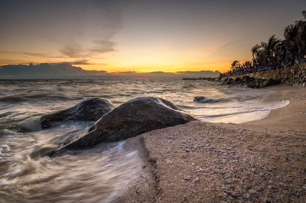 Die welle am strand mit sonnenuntergangshimmel