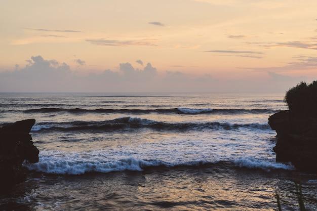 Die wellen des ozeans brechen gegen die felsen. planschen ozean wellen bei sonnenuntergang.