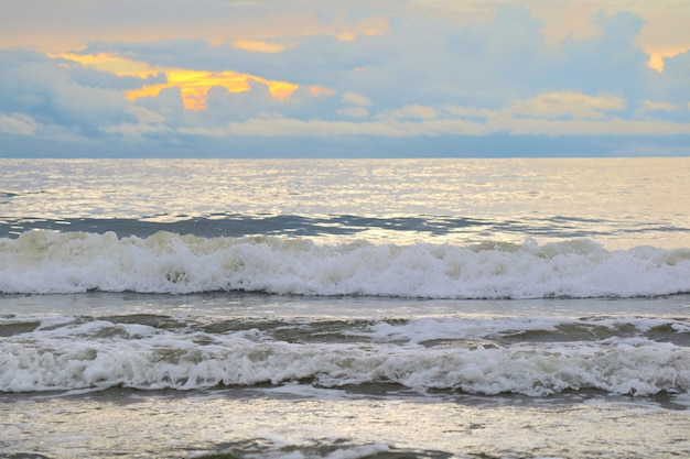 Die wellen schlagen am strand mit orange himmel und weißen wolken im mondschein