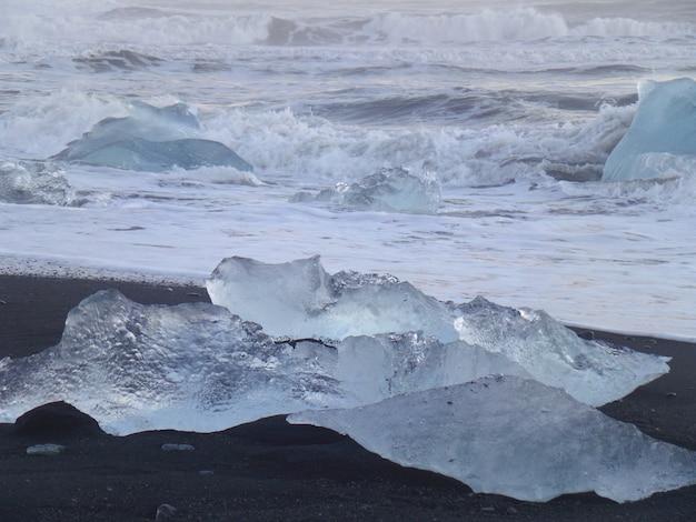 Die wellen schlagen eisberge am schwarzen sandstrand, südisland