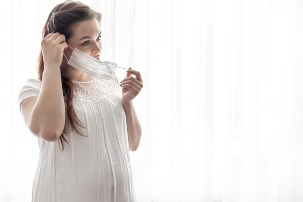 Die werdende mutter in einem weißen t-shirt mit einer schutzmaske gegen das coronavirus im gesicht.