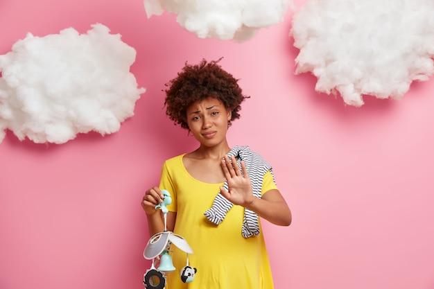 Die werdende mutter macht eine ablehnungsgeste, hält die handfläche in ablehnung, hat einen schwangeren runden bauch und posiert mit babyartikeln an der rosa wand mit weißen wolken. elternschaft und mutterschaft.
