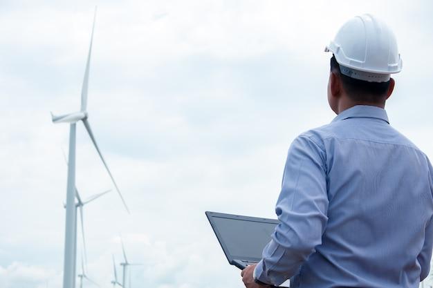 Die windmühlen der ingenieure arbeiten an einem laptop mit der windkraftanlage dahinter