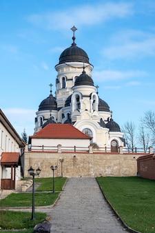 Die winterkirche und der innenhof des capriana-klosters. kahle bäume und grüne rasenflächen, gutes wetter in moldawien