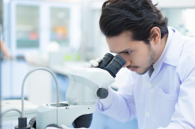 Die wissenschaftler asian benutzen ein mikroskop