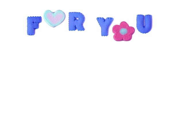Die wörter für sie buchstabiert mit blauen keksen in alphabetform und rosa marshmallow auf weißem hintergrund