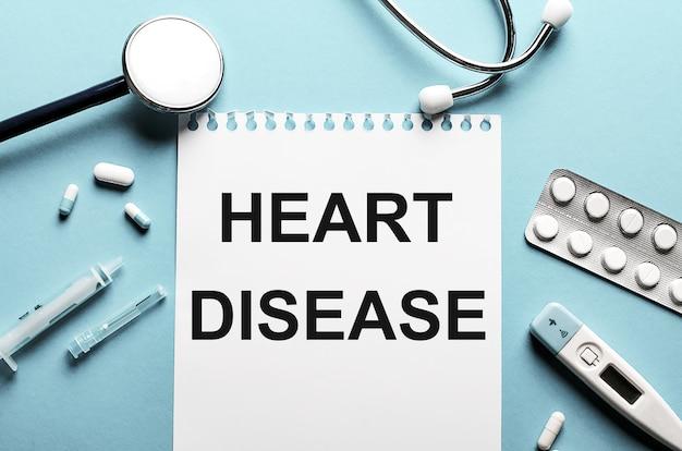 Die wörter herzkrankheit geschrieben auf einem weißen notizblock auf einem blauen hintergrund nahe einem stethoskop, einer spritze, einem elektronischen thermometer und pillen. medizinisches konzept