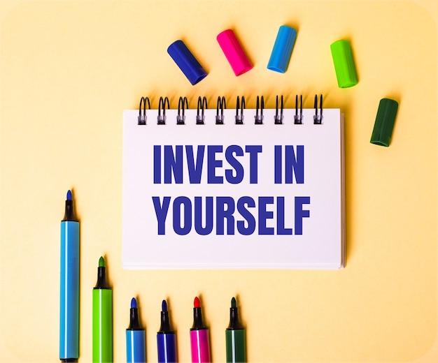 Die wörter investieren in sich selbst geschrieben in einem weißen notizbuch auf einer beigen oberfläche nahe mehrfarbigen markierungen
