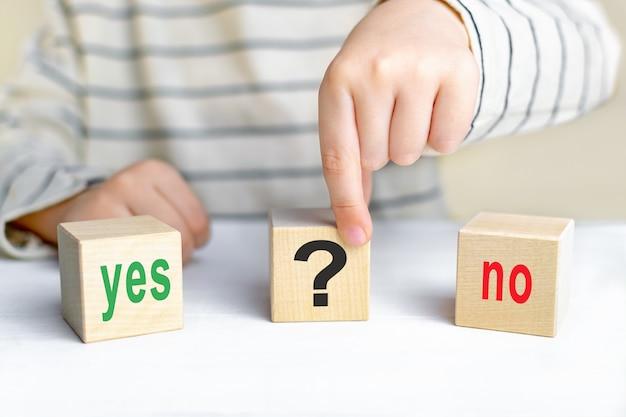 Die wörter ja und nein und ein fragezeichen auf holzwürfeln. das konzept der auswahl der richtigen lösung