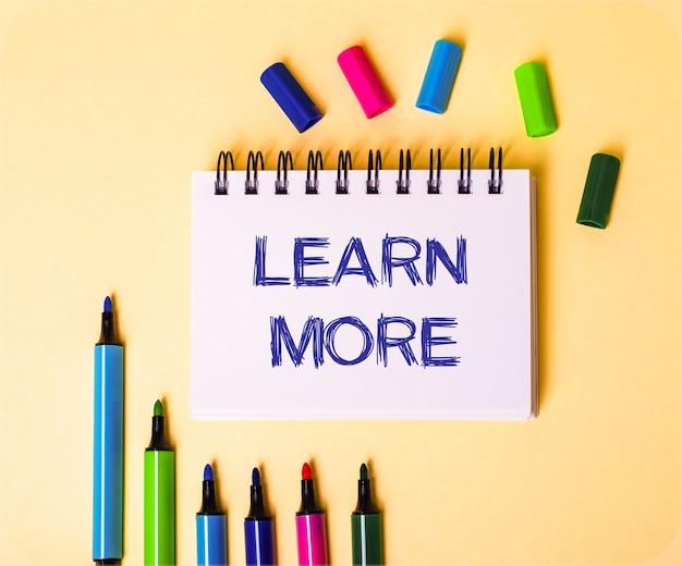 Die wörter lernen mehr geschrieben in einem weißen notizbuch auf einem beigen hintergrund nahe mehrfarbigen markierungen.