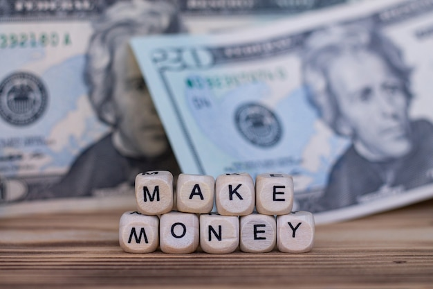 Die wörter machen geld, gezeichnet mit buchstaben auf holzwürfeln auf dem hintergrund von dollarnoten.