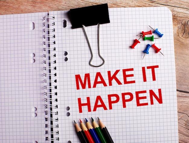 Die wörter make it happen sind in einem notizbuch in der nähe von mehrfarbigen stiften und knöpfen auf einem hölzernen hintergrund geschrieben.