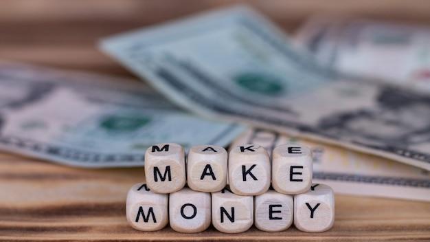 Die wörter make money, ausgekleidet mit buchstaben auf holzwürfeln auf der oberfläche von dollarnoten