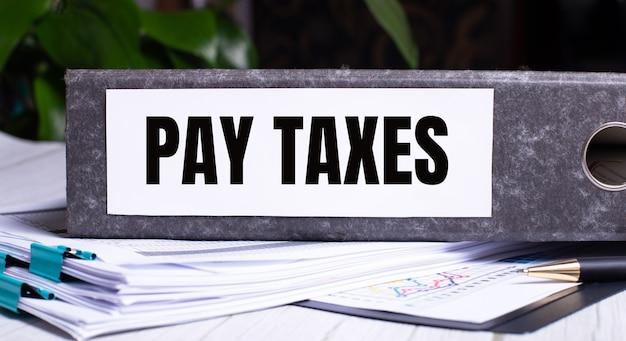 Die wörter pay taxes werden in einen grauen dateiordner neben dokumenten geschrieben